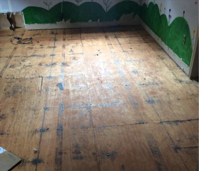 Wooden subfloor in a room with green hills painted along the wall
