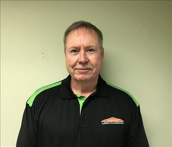 Headshot of half-smiling man wearing a SERVPRO uniform in front of bland background