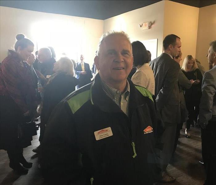 Man in SERVPRO jacket standing in a crowd of people