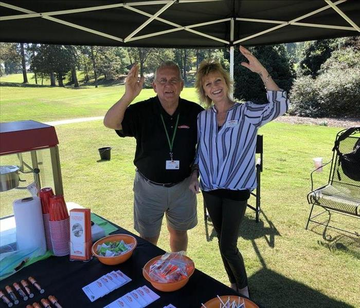 Two SERVPRO employees posing under a tent on golf greens