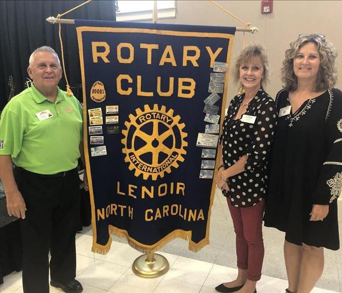 Three SERVPRO employees standing next to dark blue Lenoir Rotary Club banner