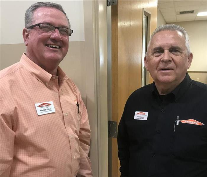 Two SERVPRO employees standing side-by-side in front of an open entryway