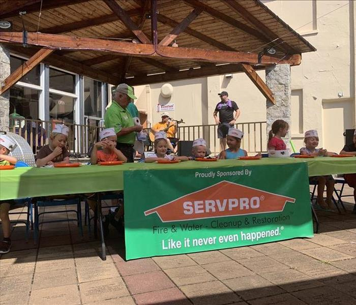 Children wearing paper hats sit at light-green table with SERVPRO banner on the front
