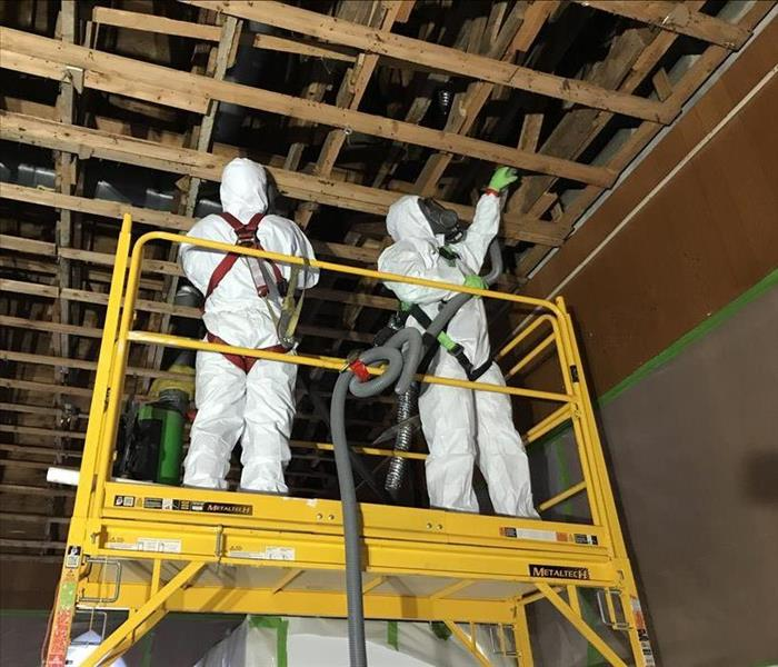 Two people in white PPE standing on a lift cleaning an exposed ceiling