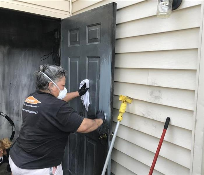 Female SERVPRO employee wearing a mask wipes down a soot-covered door