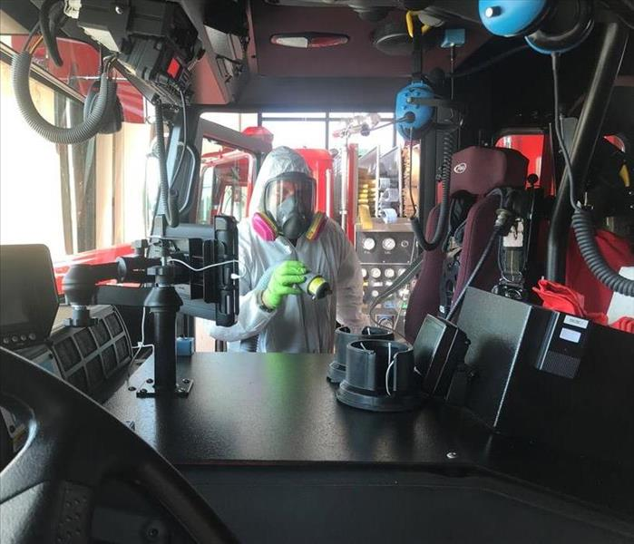 SERVPRO employee in PPE holding a tube inside a fire truck