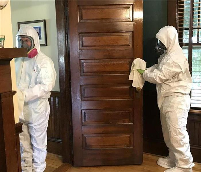 Two people in white PPE wiping down surfaces in a room