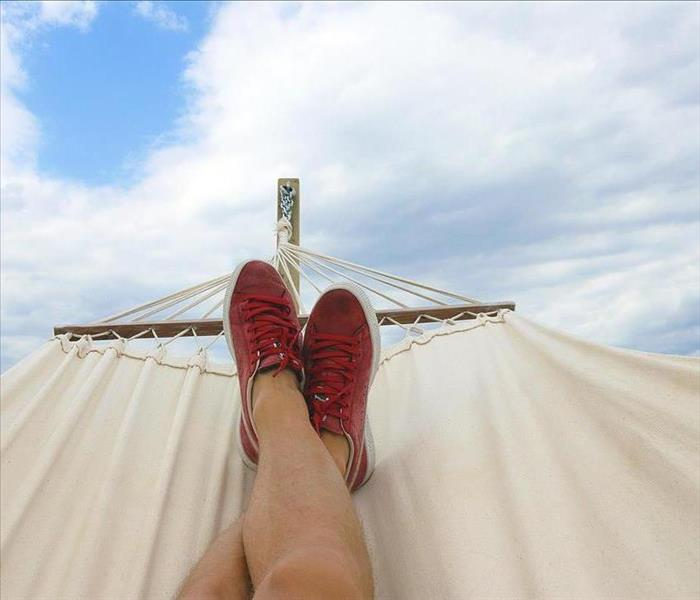 Person wearing red low-top shoes resting on a hammock
