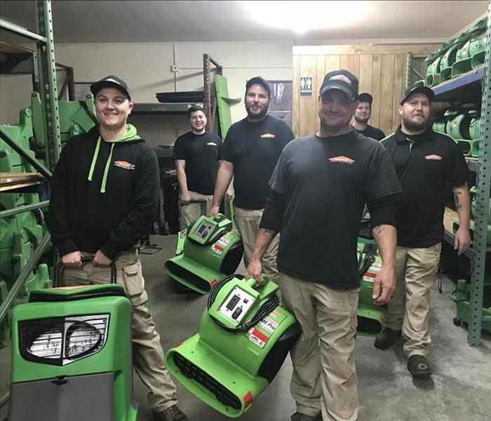 Six SERVPRO employees posing with green air movers and a dehumidifier