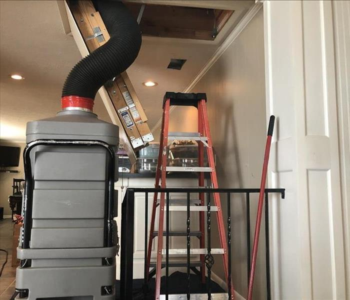Black tube of gray vacuum enters attic above cluttered room