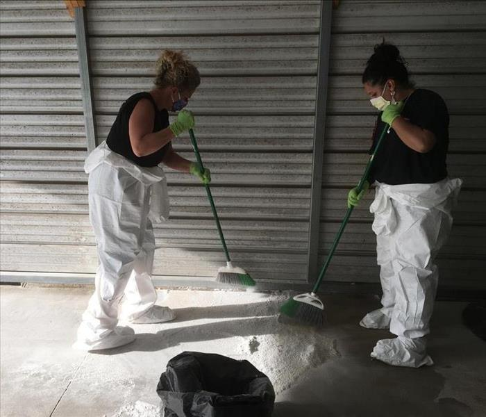 Two women wearing face masks, gloves, and partial PPE sweeping white substance on the floor
