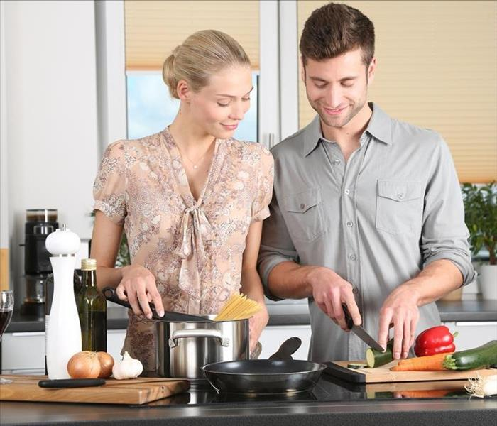 Couple in a kitchen chopping vegetables and stirring spaghetti in a pot
