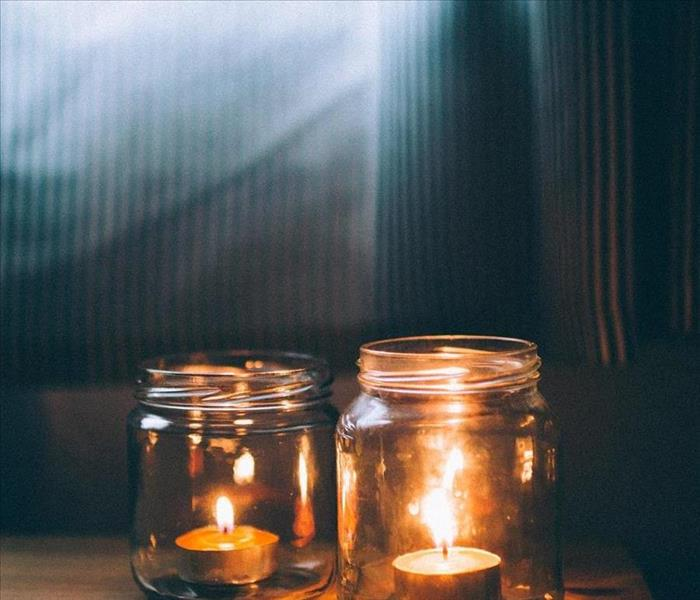 Two candles in jars on a wooden table by a curtained window