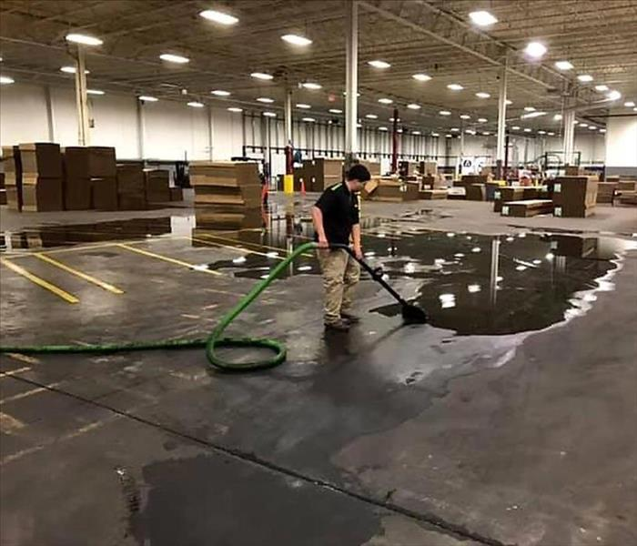 SERVPRO employee extracting water from large puddle in a warehouse